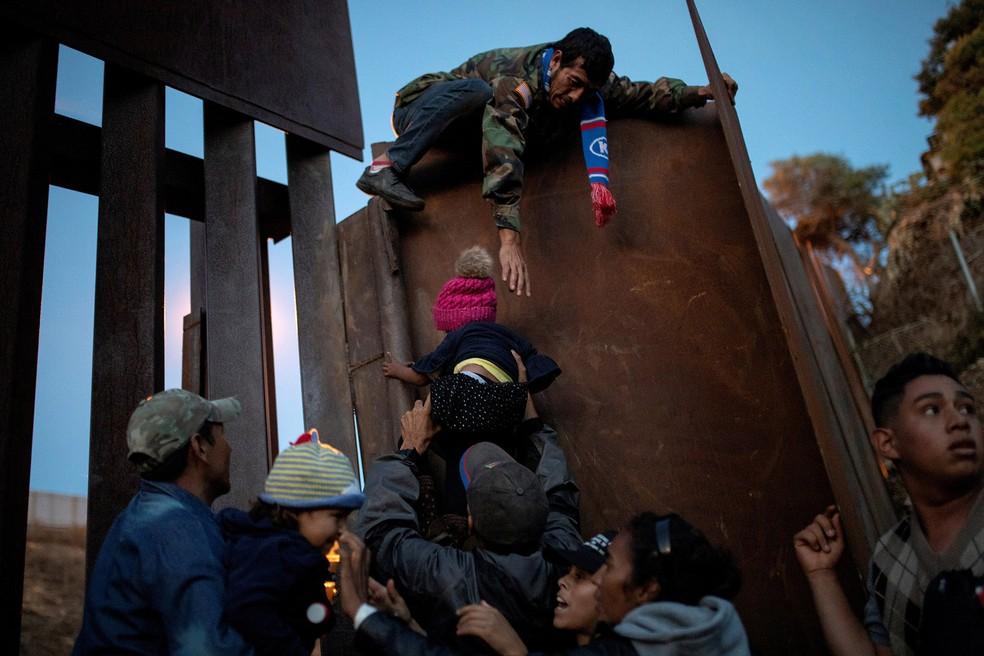 Migrantes hondurenhos atravessam uma criança por cima do muro na fronteira entre México e EUA perto de Tijuana, no domingo (2). Eles viajaram na caravana que reuniu cerca de 6 mil pessoas da América Central, a maioria de Honduras — Foto: Alkis Konstantinidis/Reuters