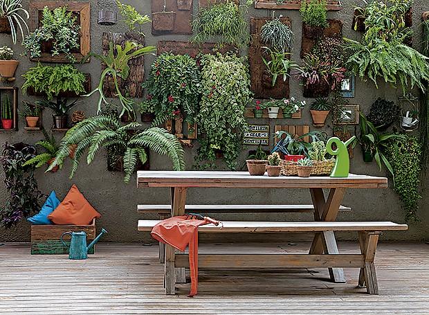 Área externa: ao lado da churrasqueira, a mesa de madeira da Tok & Stok é usada pelos moradores para reunir família e amigos. Eles criaram juntos o jardim vertical, com plantas dispostas em painéis de fibra de coco (Foto: Lufe Gomes/ Editora Globo)