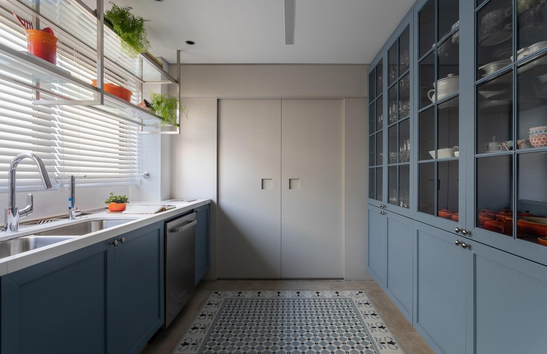Ambiente de cozinha com piso com ladrilhos hidráulicos, armário e gabinete azul.