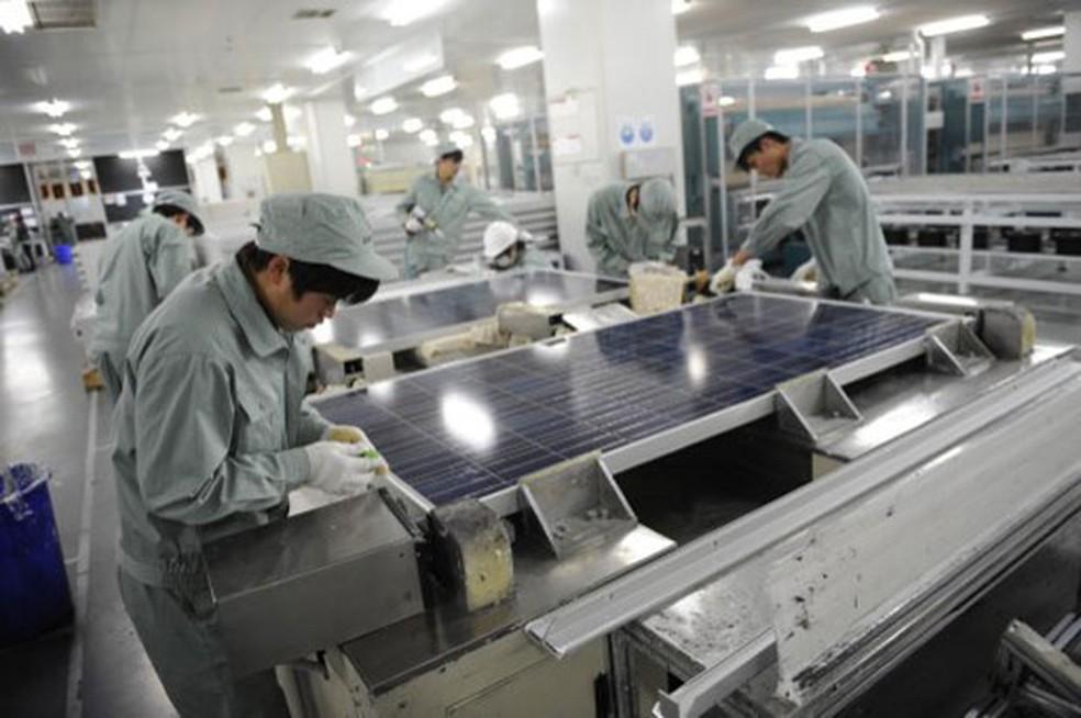 Trabalhadores montando painel solar na companhia chinesa Suntech — Foto: Peter Parks/AFP