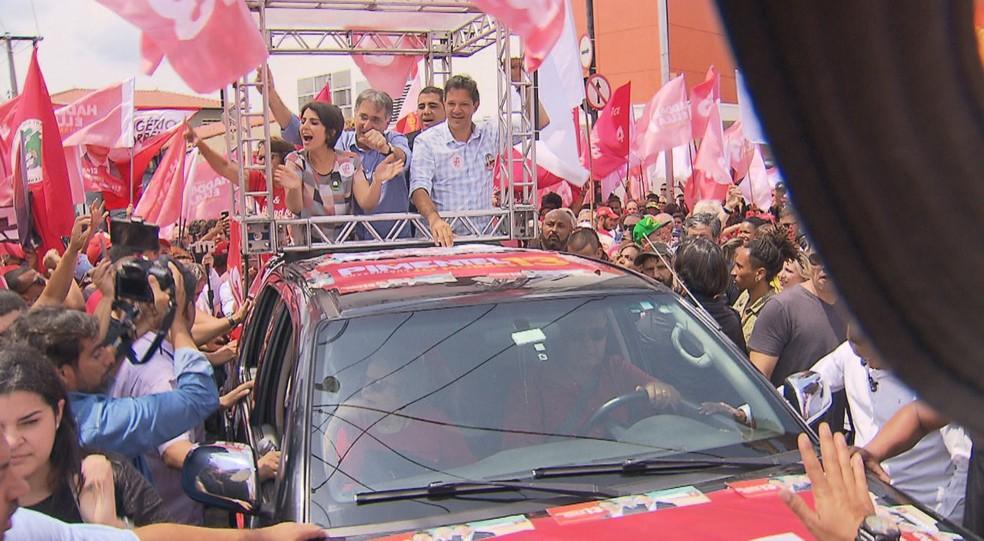 Ao lado da vice na sua chapa, Manuela D'Ávila, Fernando Haddad (à direita) faz campanha em cima de caminhonete — Foto: Reprodução / TV Globo