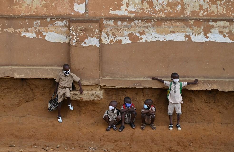 Crianças em idade escolar sentam-se do lado de fora da sala de aula em uma escola primária em Attecoube, popular distrito de Abidjan, na Costa do Marfim, na segunda-feira (25), no 1º dia após o reinício das aulas após o bloqueio por causa da pandemia de Covid-19 — Foto: Issouf Sanogo / AFP