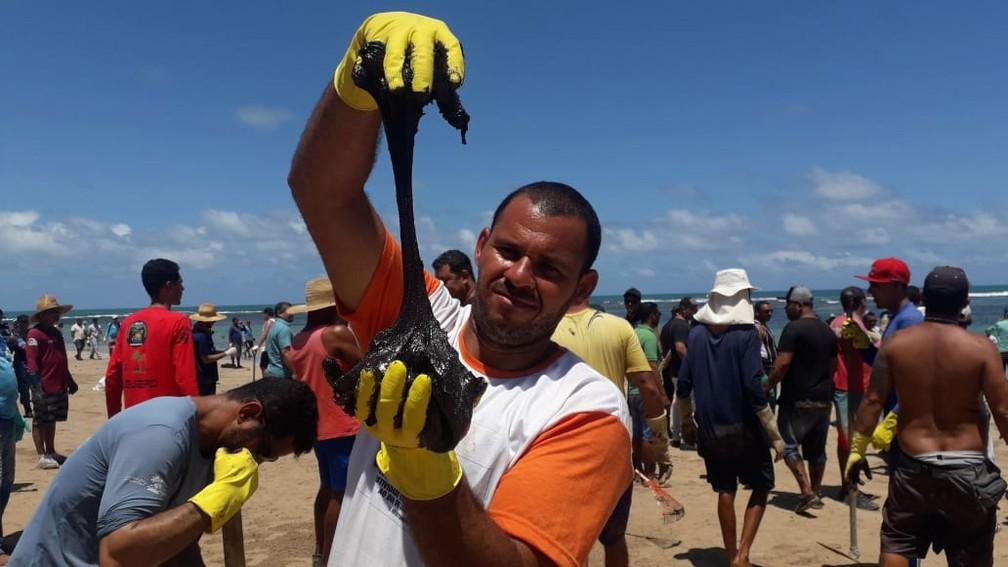 Voluntários retiram óleo da praia do Cupe, em Ipojuca, no litoral Sul de Pernambuco — Foto: Luna Markman/GloboNews