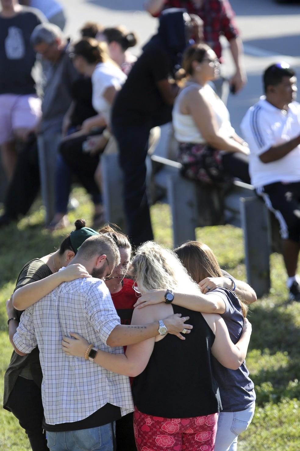 Familiares rezam em frente à escola Marjory Stoneman Douglas High School, em Parkland, na Flórida, onde um tiroteio deixou mortos e feridos (Foto: Amy Beth Bennett/South Florida Sun-Sentinel via AP)