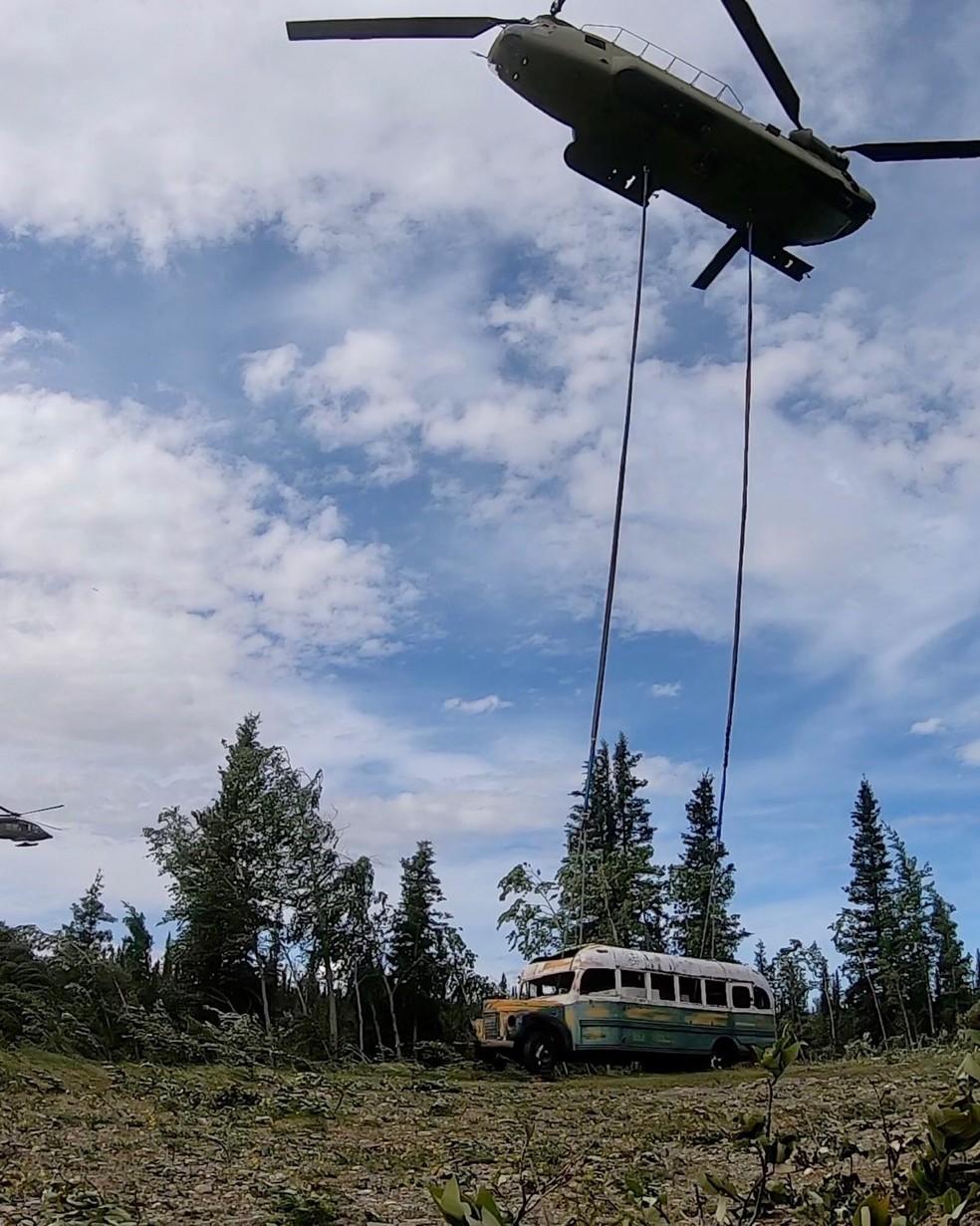 Helicóptero levanta ônibus que ficou famoso no livro e no filme 'Na natureza selvagem' sobre o Parque Nacional de Denali, no Alasca — Foto: Seth Lacount/Guarda Nacional do Exército do Alasca/AFP