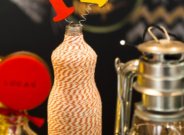 Sabe aquela garrafa de vidro que iria para o lixo?  Ela pode muito bem se tornar parte da decoração quando estilizada. Aqui, foi usado um barbante e molinhas com números ou letras.  (Foto: Divulgação/Sandra Pagano)