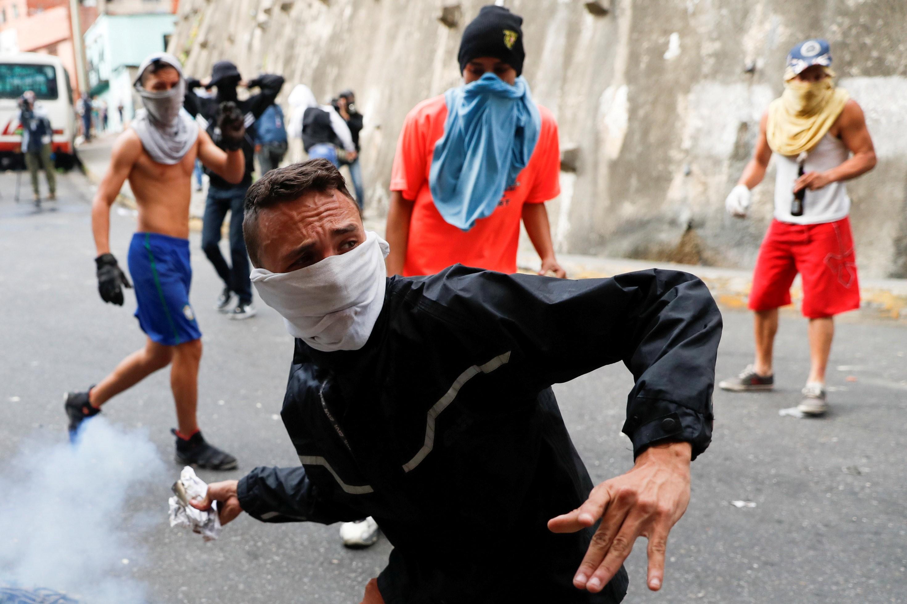 Manifestante joga de volta uma bomba de gás lacrimogêneo durante  protesto
