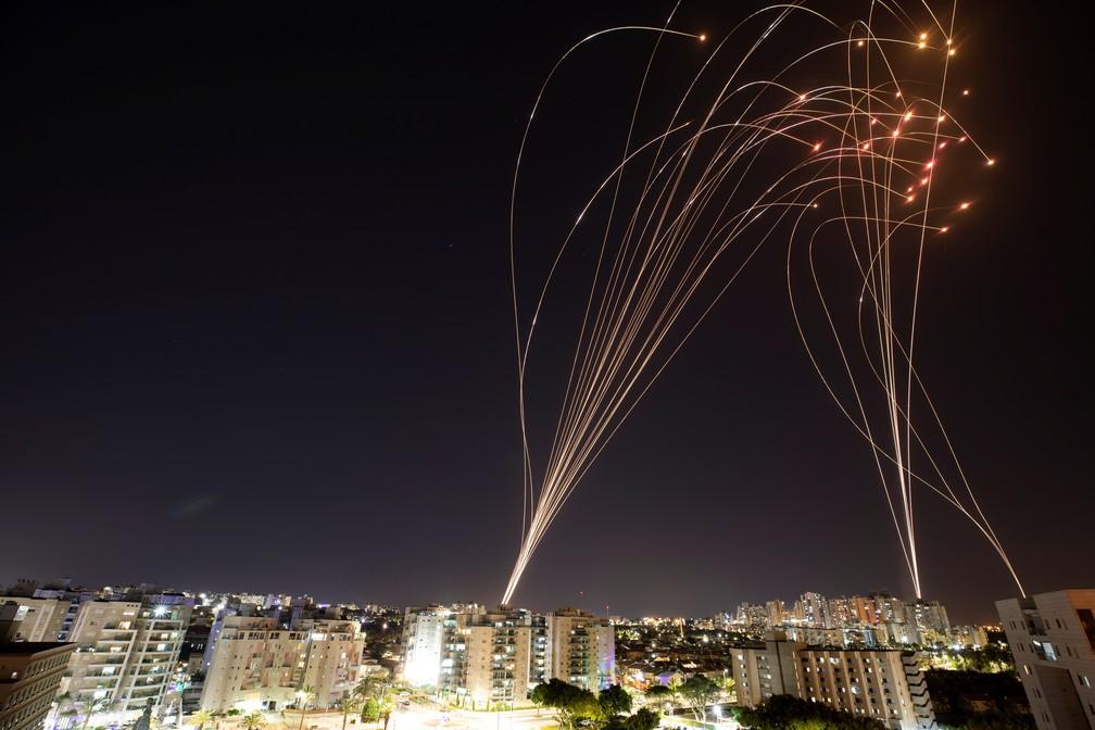 Rastros de luz do sistema antimísseis de Israel em ação na cidade de Ashkelon na noite de terça (11) — Foto: Nir Elias/Reuters