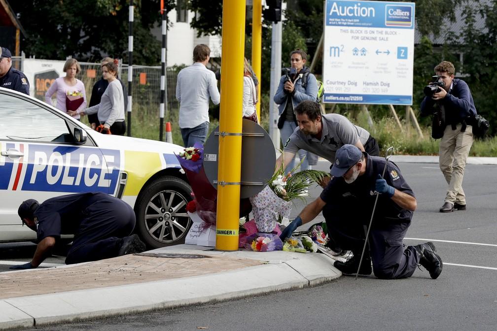 Policiais vasculham área perto da mesquita Masjid Al Noor, em Christchurch, na Nova Zelândia. O local sofreu atentado na sexta-feira e recebeu flores para homenagear vítimas — Foto: Mark Baker/AP Photo