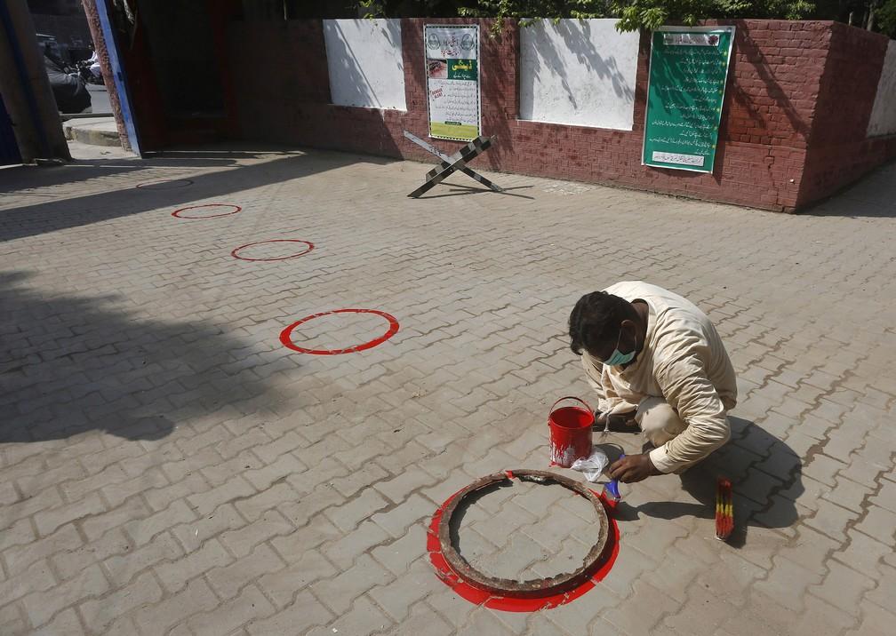 14 de setembro - Homem pinta círculos para distanciamento social em escola como preparação para a reabertura, em Lahore, no Paquistão — Foto: K.M. Chaudary/AP