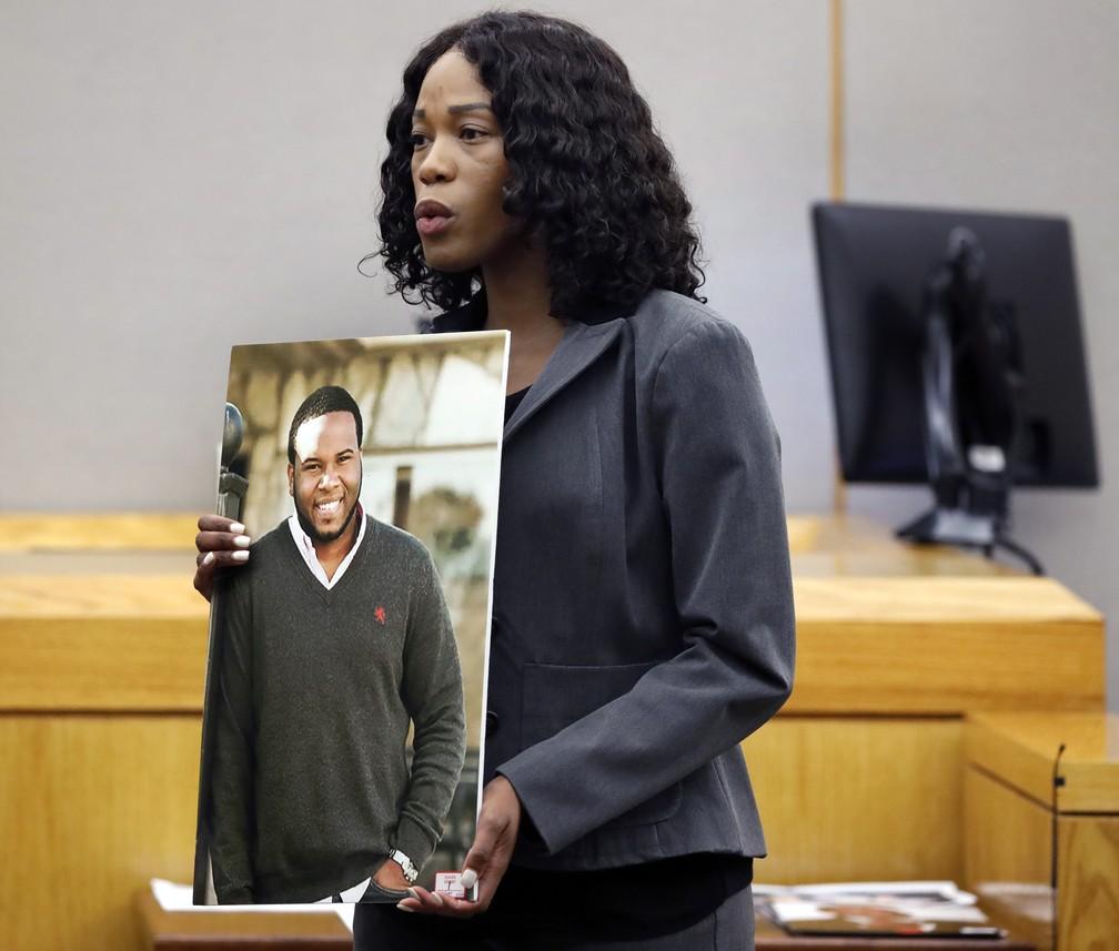 A promotora distrital assistente Mischeka Nicholson segura uma foto de Botham Jean diante do júri pouco antes da leitura da sentença na quarta-feira (2). A promotoria do caso pediu que a ex-policial fosse condenada a 28 anos de prisão; ela recebeu uma pena de dez anos. — Foto: Tom Fox/The Dallas Morning News via AP