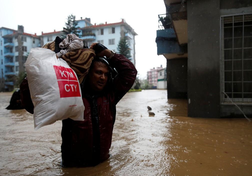 Homem carregando pertences anda em meio às inundações que atingiram Kathmandu, no Nepal, no dia 12 de julho. — Foto: Navesh Chitrakar/Reuters