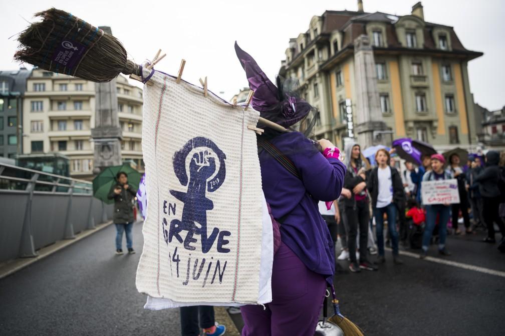 """Manifestante com faixa que diz """"em greve no dia 14 de junho"""" em Lausanne, na Suíça, nesta sexta-feira (14). — Foto: Keystone via AP"""