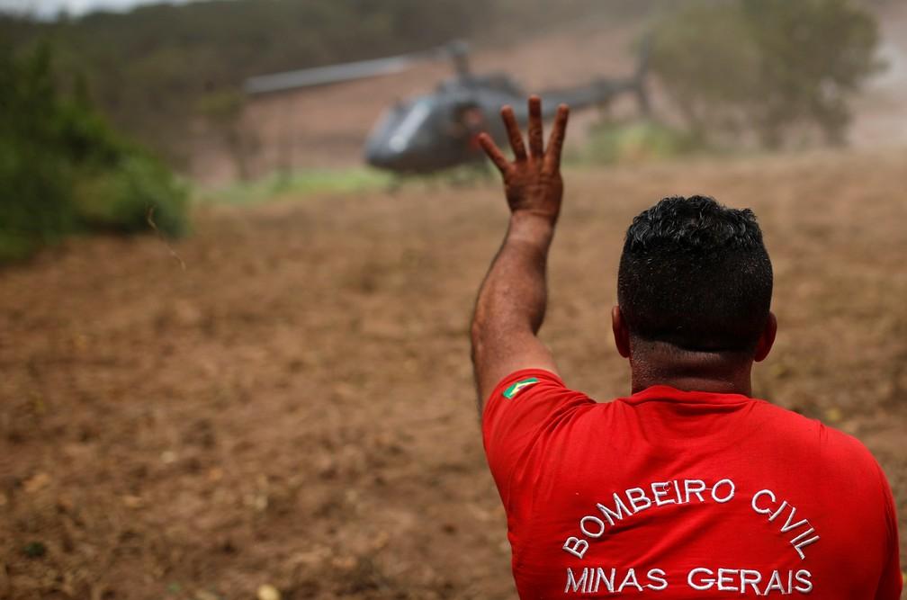 Bombeiro gesticula perto de um helicóptero de resgate dois dias depois do rompimento da barragem da Vale em Brumadinho. — Foto: Adriano Machado/Reuters