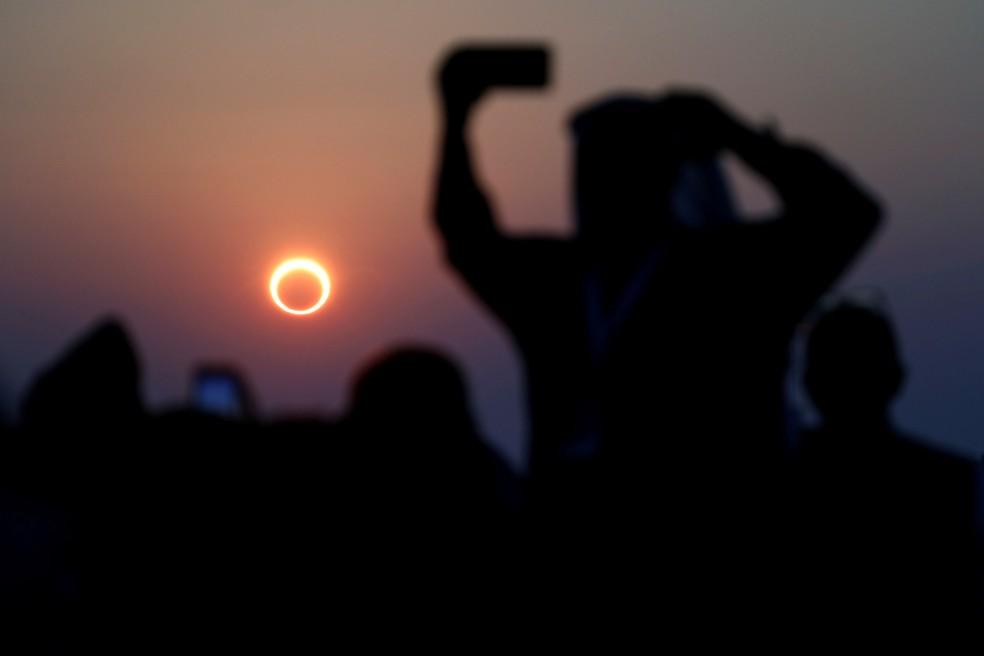 Pessoas tiram fotos com seus smartphones enquanto monitoram o eclipse solar anular na Arábia Saudita, em 2019 — Foto: Hamad I Mohammed/Reuters