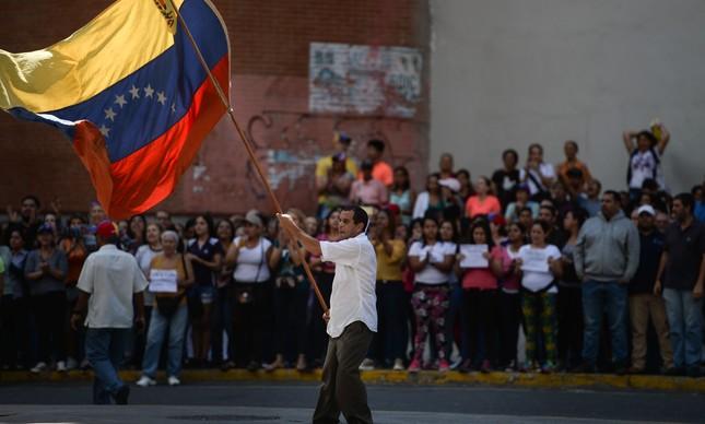 Manifestante balança bandeira da Venezuela em Caracas