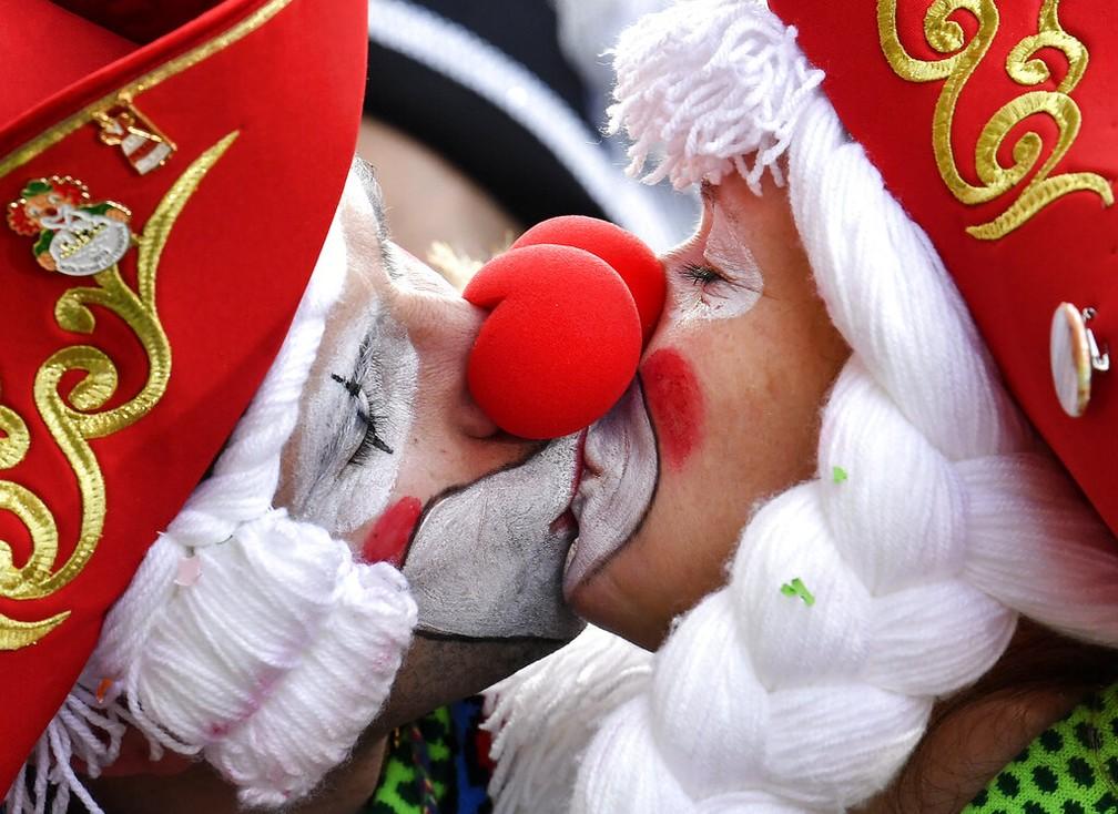 Foliões se beijam durante desfile carnavalesco nas ruas de Colônia, na Alemanha. — Foto: Martin Meissner/AP