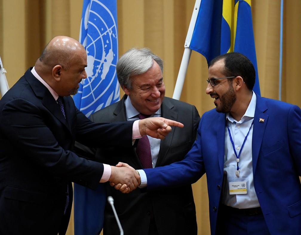 Representante da delegação houthi, Mohammed Abdul-Salam (à direita), e ministro das Relações Exteriores do Iêmen, Khaled al-Yaman (E), se cumprimentam próximo ao secretário-geral da ONU António Guterres — Foto: TT News Agency/Pontus Lundahl via Reuters
