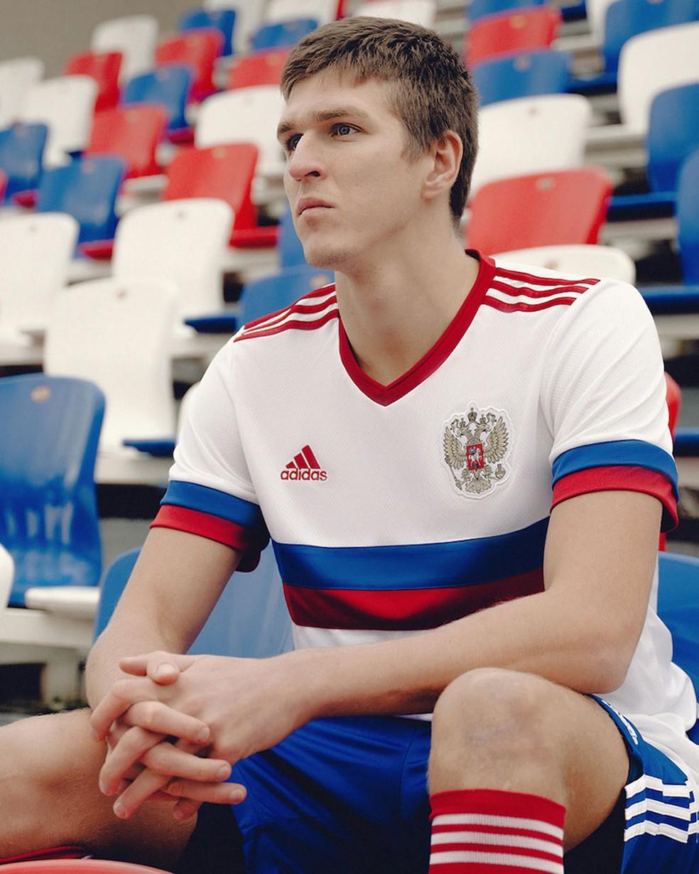 O atacante Sobolev posa com a nova camisa reserva da Rússia — Foto: Divulgação/Adidas