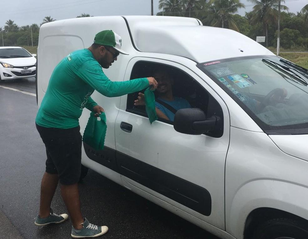 Projeto Nossa Praia distribui sacolas de lixo para os carros e orienta que não sejam jogados resíduos  no meio ambiente (Foto: Andréa Resende/G1)