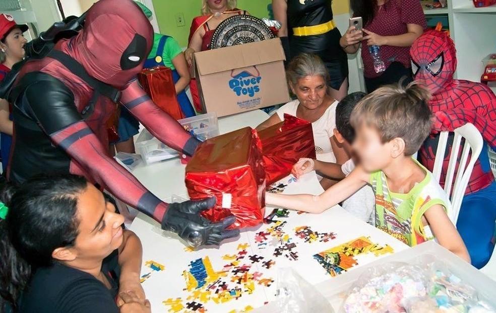 Caracterizado como Deadpool, o funcionário público Fábio Nunes da Silva presenteia crianças — Foto: Fábio Nunes da Silva/Arquivo pessoal