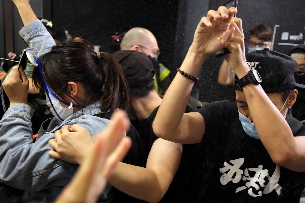 Manifestantes reagem quando a polícia de choque os dispersa com spray de pimenta durante protesto dentro de um shopping center, em Hong Kong — Foto: Tyrone Siu/Reuters
