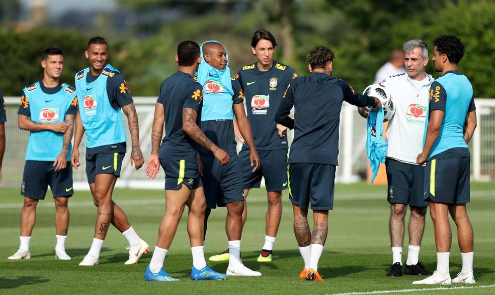 Jogadores da seleção brasileira distriubuem coletes (Foto: Reuters)