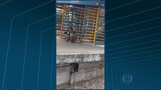 Homem rasteja para passar por roleta em estação de trem do Rio