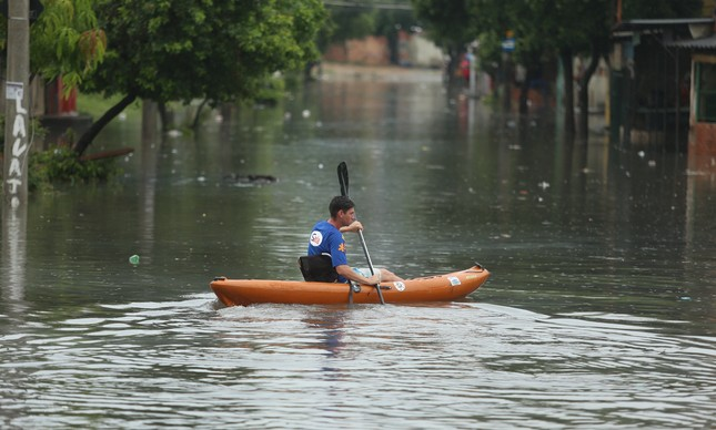 Homem rema em canoa na Rua Ouseley, em Acari, após chuva em janeiro de 2018