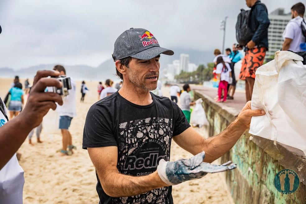 Carlos Burle ajuda na coleta de lixo — Foto: Alexandre Socci / Divulgação