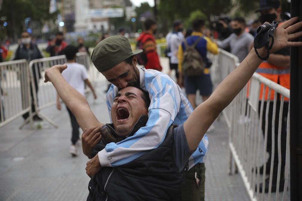 Argentino chora e é amparado pelo amigo na Plaza de Mayo, em frente à Casa Rosada, onde o corpo de Diego Maradona é velado — Foto: Rodrigo Abd/AP