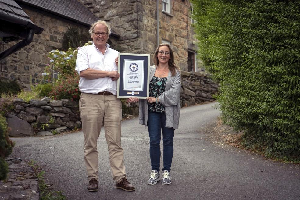 Gwyn Headley e Sarah Badhan seguram o certificado de rua mais íngreme do mundo, dado à via Pen Llech. — Foto: Andrew Davies/Guinness World Records via AP