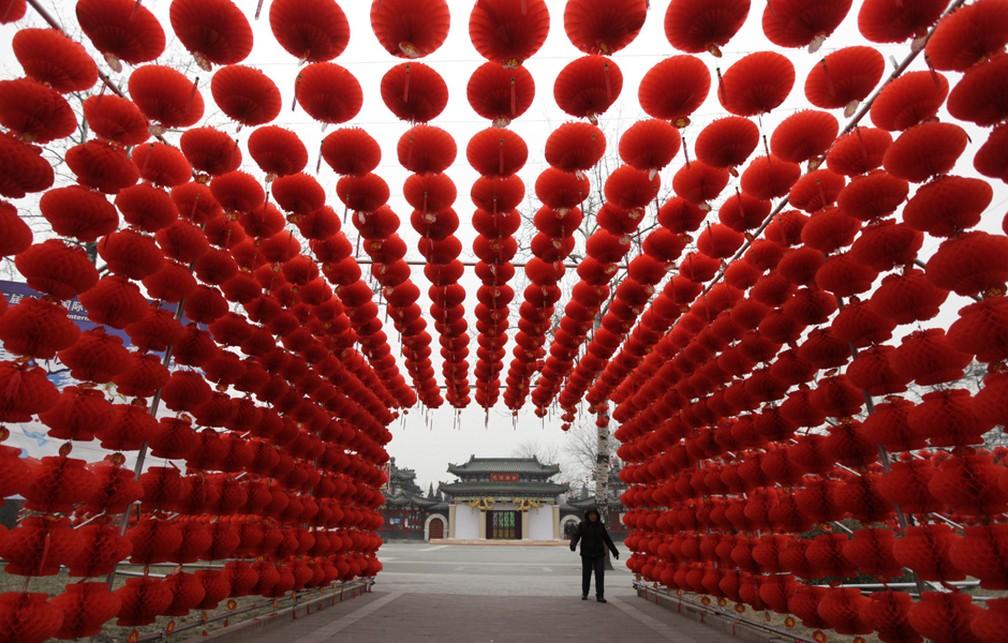 Mulher passa por lanternas vermelhas colocadas como decoração para uma feira do templo em uma entrada do parque Longtan em Pequim em 2016 — Foto: Reuters