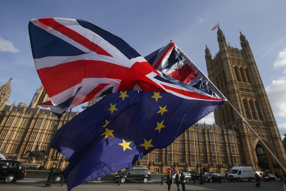 -  Manifestantes protestam com uma bandeiras do Reino Unido e da União Europeia em frente ao Parlamento em Westminster, no centro de Londres, nesta quin
