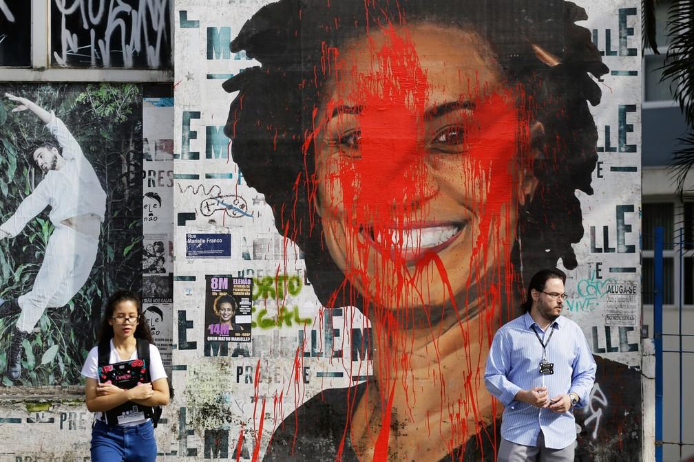 Imagem da vereadora assassinada Marielle Franco é vista manchada com tinta vermelha na Avenida Consolação, no centro de São Paulo, na manhã desta terça-feira (12). Uma operação conjunta prendeu dois suspeitos de matar Marielle e o motorista Anderson Gomes: Ronie Lessa, policial militar reformado, e Elcio Vieira de Queiroz, expulso da PM — Foto: Nelson Antoine/Estadão Conteúdo