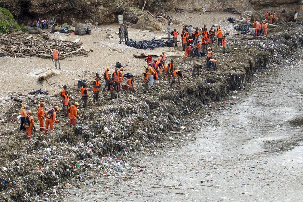 Trabalhadores do Ministério de Obras Públicas e Comunicações (MOPC) coletam lixo das praias de Güibia, Montesino e ao lado do Obelisco feminino na região do Malecon, em Santo Domingo, em 16 de julho de 2018. O MOPC iniciou as obras de limpeza para remover toneladas de resíduos sólidos da costa do Malecon de Santo Domingo, após a tempestade subtropical Beryl passou. (Foto: Erika SANTELICES / afp)