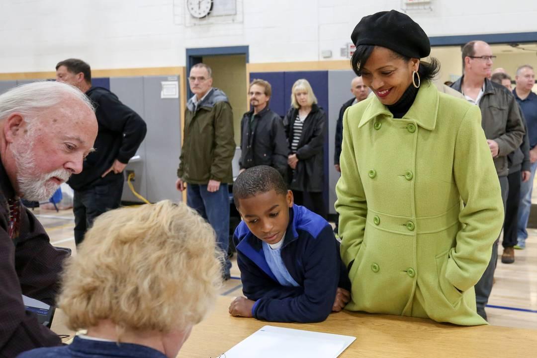 Candidata democrata à Câmara dos Representares, Jahana Hayes chega para votar ao lado de seu filho Myles em colégio em Wolcott, Connecticut