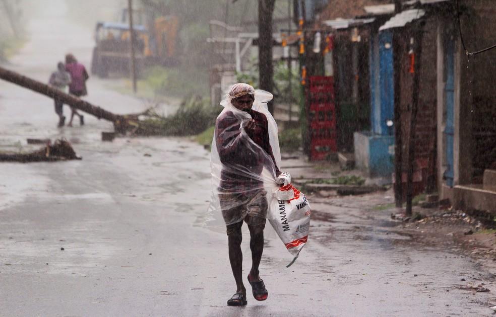Homem se protege com plástico enquanto caminha provocada pelo ciclone Amphan, no distrito de Bhadrak, no estado indiano de Orissa, na quarta-feira (20) — Foto:  Associated Press