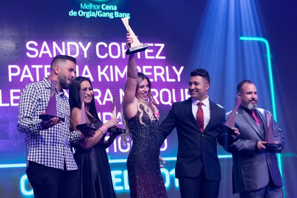 Tony Tigrão (à esquerda), Patrícia Kimberly (ao centro) e Loupan (de terno) recebem o troféu de Melhor Cena de Orgia/Ganga Bang no Prêmio Sexy Hot 2018 ? Foto: Celso Tavares/G1