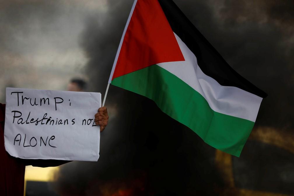 Manifestante segura bandeira palestina e cartaz contra Trump durante protesto (Foto: Mohamad Torokman/Reuters)