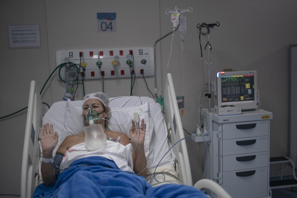 Eliane Lima, de 56 anos, reza enquanto é tratada para Covid-19 com máscara de oxigênio na UTI do Hospital Ernesto Che Guevara, em Maricá, no Rio de Janeiro, no dia 5 de junho.  — Foto: Mauro Pimentel/AFP