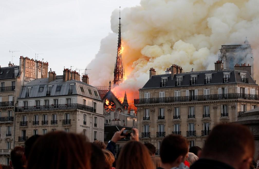 Pessoas observam de longe o grande incêndio que consome a Catedral de Notre-Dame, em Paris — Foto: Benoit Tessier/Reuters