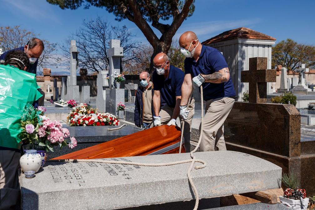 29 de março - Funcionários de uma funerária usam máscaras durante o enterro de uma vítima de coronavírus COVID-19 no cemitério de Fuencarral em Madri, na Espanha — Foto: Baldesca Samper/AFP