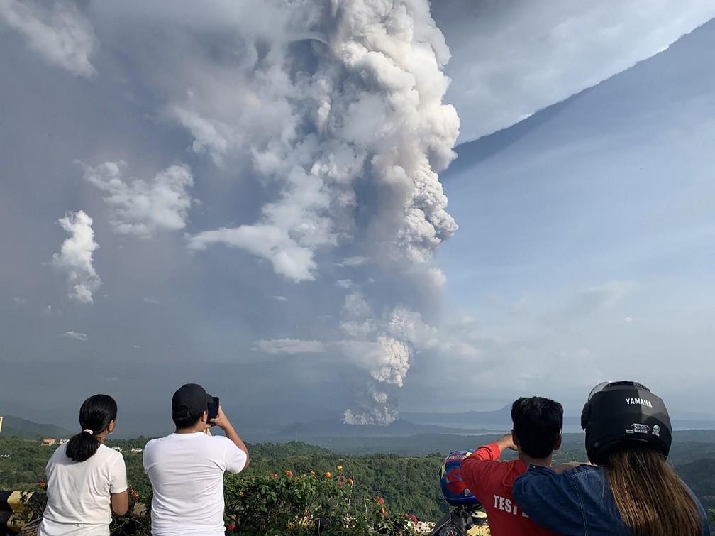Pessoas tiram fotos de uma explosão freática do vulcão Taal, nas Filipinas, em 12 de janeiro de 2020 — Foto: Bullit Marquez / AFP