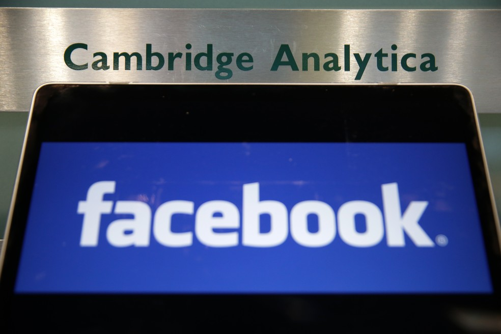 Laptop com o logo do Facebook em frente a letreiro do prédio da Cambridge Analytica, em Londres. — Foto: Daniel Leal-Olivas/France Presse