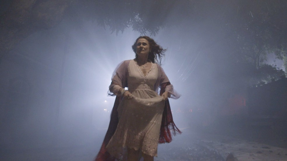 Milu (Zezé Polessa) ouve um baralho misterioso e corre pela escuridão, em 'O Sétimo Guardião' — Foto: TV Globo