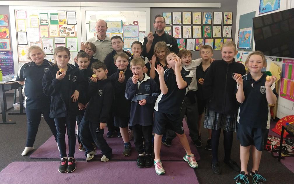 Alunos da John Paul II Catholic School, em Hobart, posam com Paul Foreman após provarem pão de queijo pela primeira vez, em 19 de agosto — Foto: Paul Foreman
