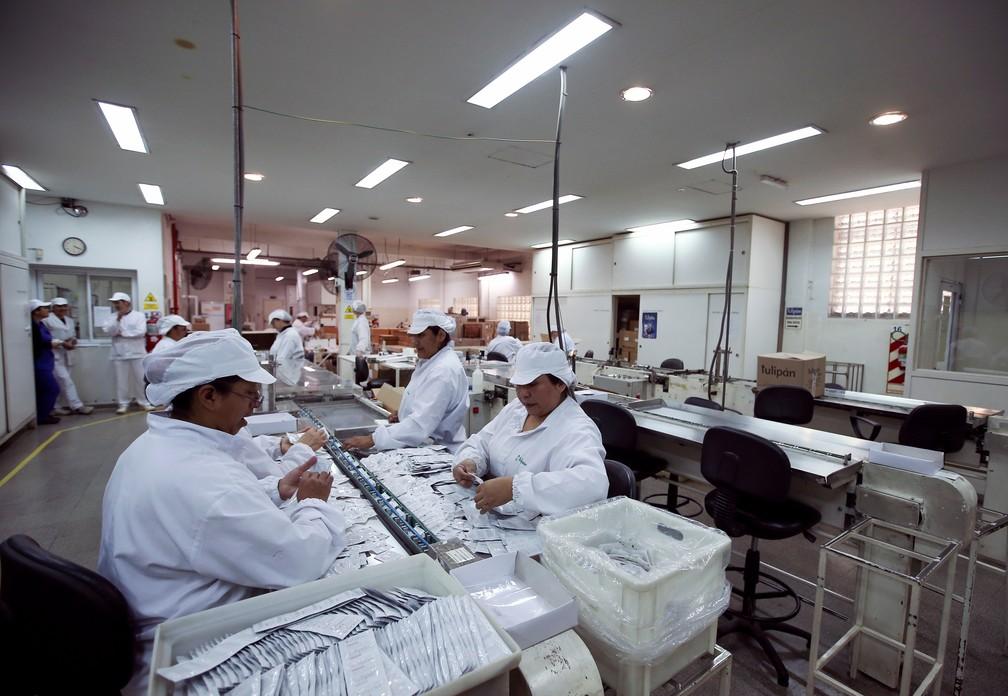 Funcionários trabalham em uma fábrica de camisinhas em Buenos Aires, Argentina — Foto: Agustin Marcarian/Reuters