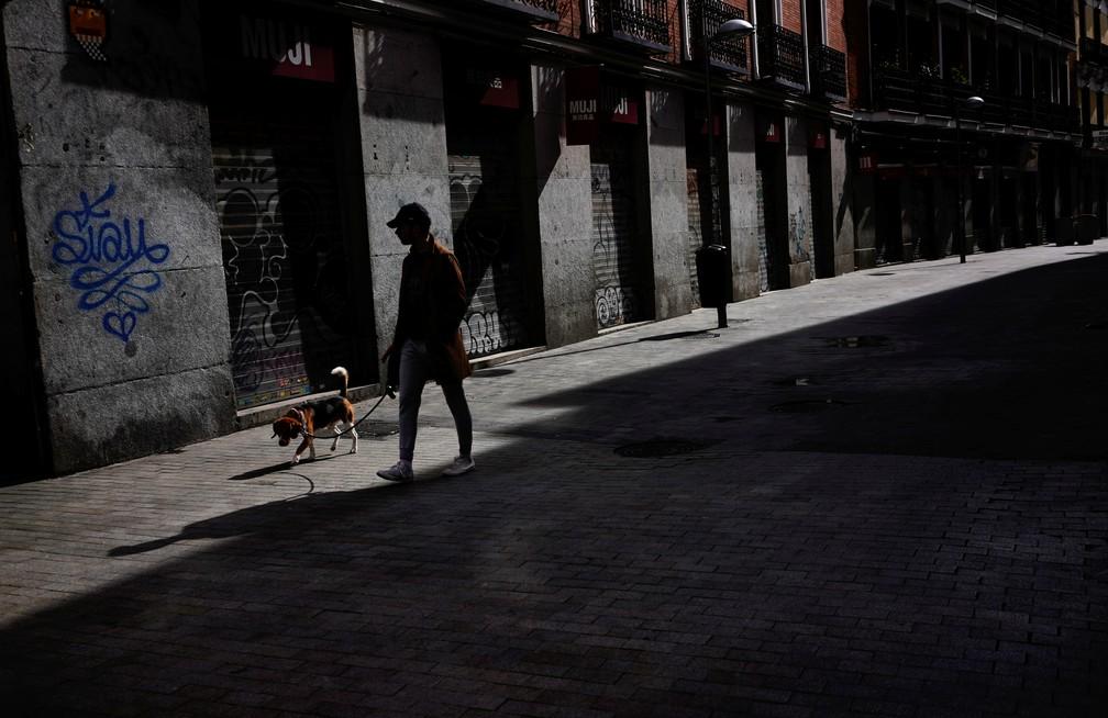 5 de abril - Homem caminha com cachorro em rua de Madrid durante quarentena, neste domingo (5) — Foto: Juan Medina/Reuters