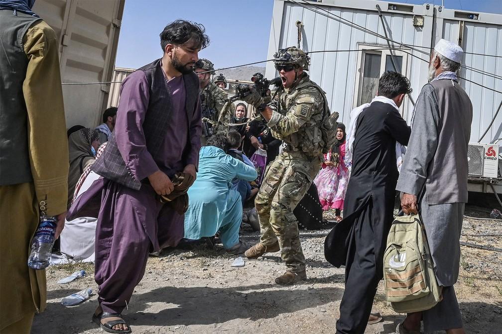 Soldado americano aponta sua arma para um passageiro afegão no aeroporto de Cabul, enquanto centenas de pessoas aguardam uma oportunidade para deixar o Afeganistão — Foto: Wakil KOHSAR/AFP